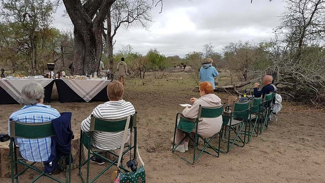 Bush breakfast at Nkorho, with guides keeping an eye on an approaching buffalo herd.